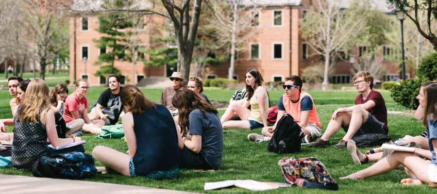 Wheaton College IL students in class sitting on the lawn outside