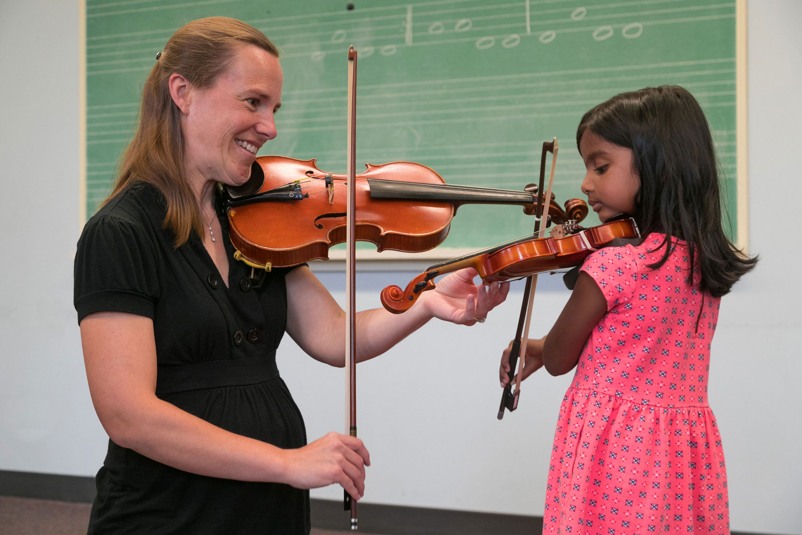 Young female child playing the violin with teacher