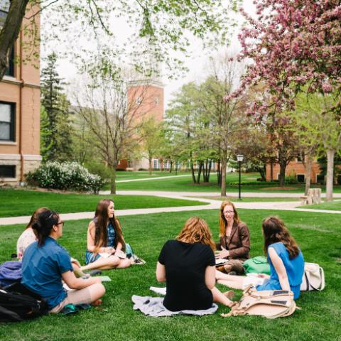 Dr. Tiffany Eberle Kriner and students sitting outside on the lawn