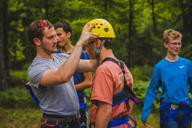 a man helping a child put on rock-climbing helmet and gear