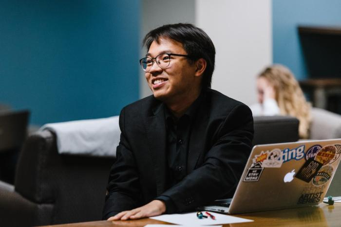 A man sitting at his laptop, looking to one side, and smiling