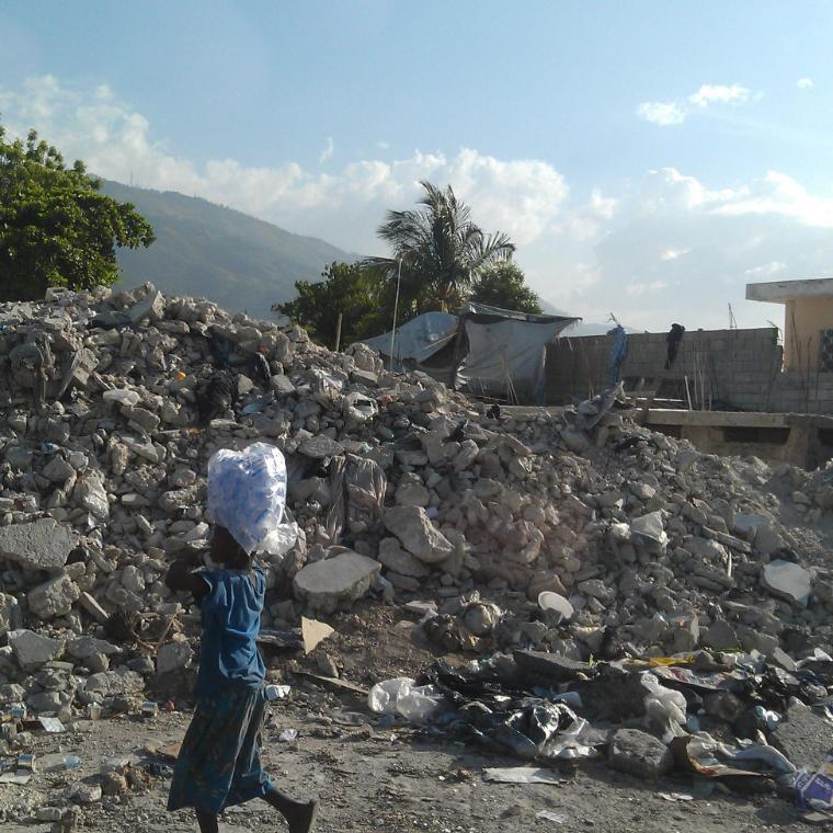 Boy balances bag on top of his head through rubble and fallen houses in Haiti after the earthquake