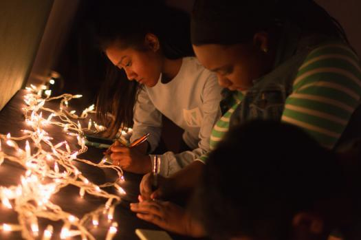 Students writing Letters by Christmas Lights