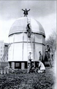 5 men standing by and on top of observatory building