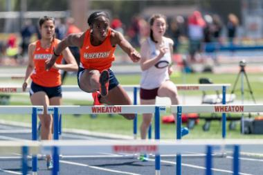 Wheaton College Women's Track Athlete Favor Ezewuzie jumping a hurdle