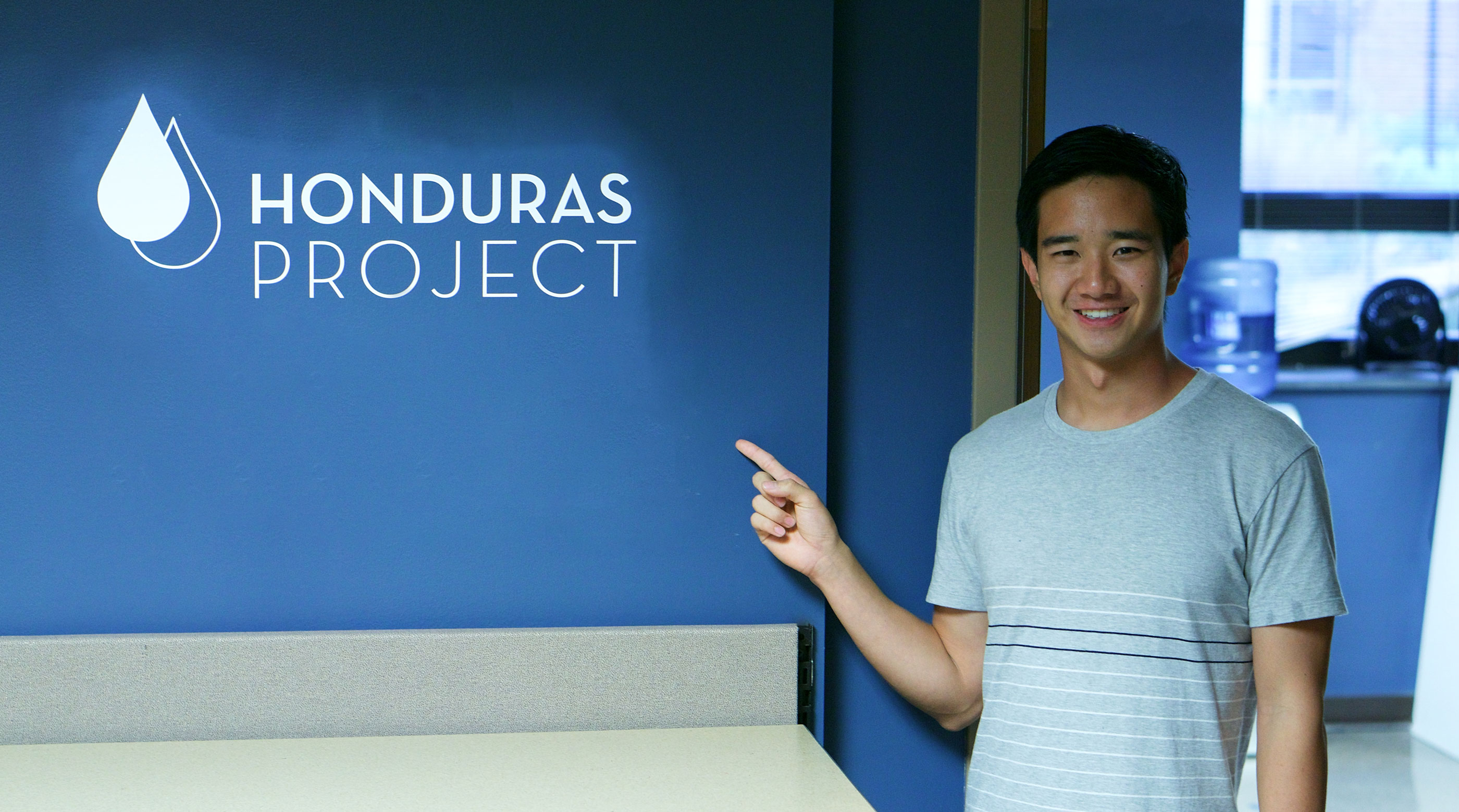 Wheaton Student pointing at Honduras Project Logo